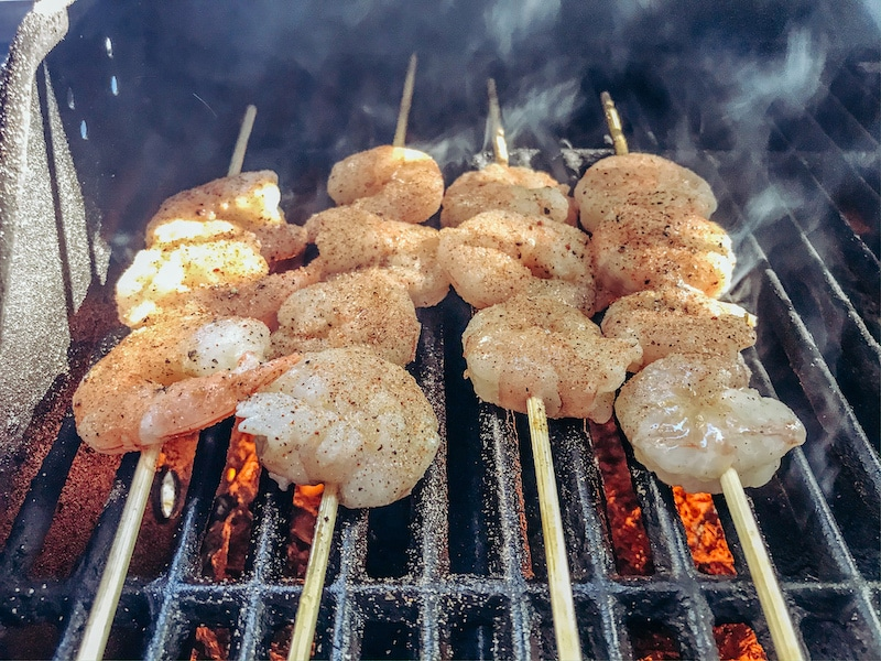 Skewers of shrimp on a grill.