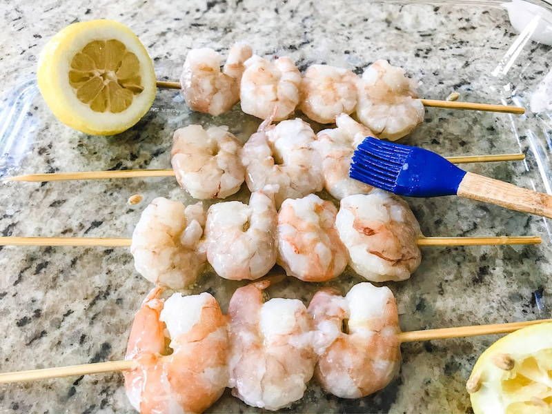Raw grilled shrimp on skewers and being brushed with butter.