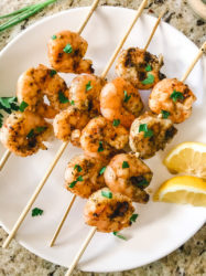 A white plate of grilled shrimp on skewers and topped with chopped parsley.