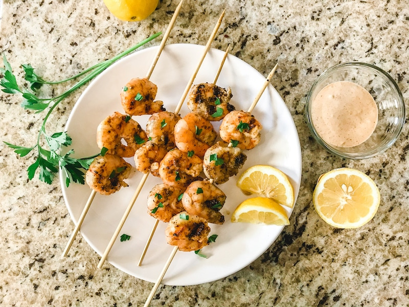 A white plate of grilled shrimp next to a sprig of Italian parsley, sliced lemons, and a small clear jar of remoulade sauce.