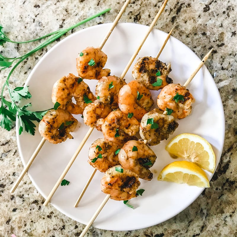 Grilled shrimp on skewers on a white plate with sliced lemons.