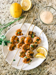 Glass bowl of Remoulade sauce above a white plate of skewered grilled shrimp.