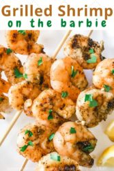 "Close up of grilled shrimp topped with chopped parsley and the words ""grilled shrimp on the barbie"" in brown and green lettering"