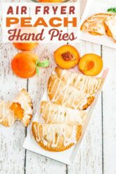 """Overhead shot of a hand pies on a white platter with the words """"air fryer peach hand pies"""" in red lettering."""