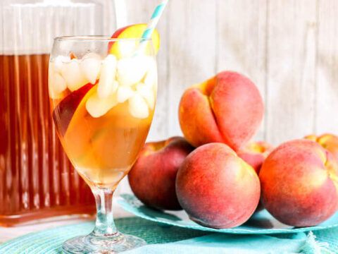 A glass of iced tea next to a plate of fresh peaches.