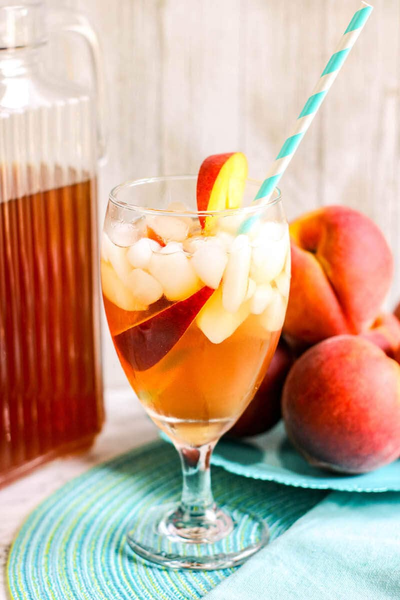 A glass of iced tea in front of a bowl of peaches and a pitcher of iced ta.