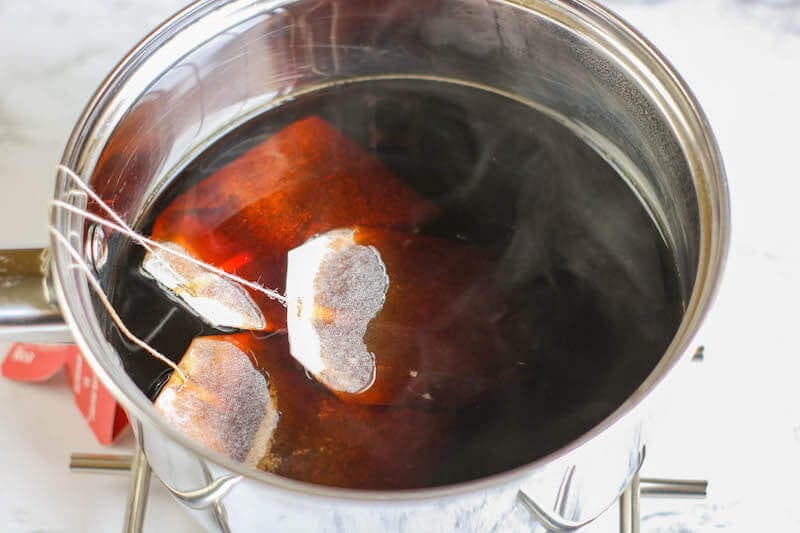 A metal pot filled with hot tea and tea bags.