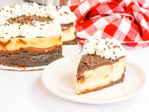 A slice of brownie cheesecake on a white plate next to the whole cheesecake.
