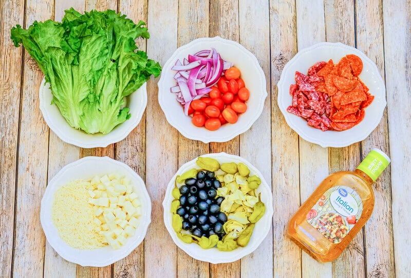 White plates arranged with the ingredients for Italian antipasto salad: romaine, tomatoes, olives, pepperoni, cheese, and dressing.
