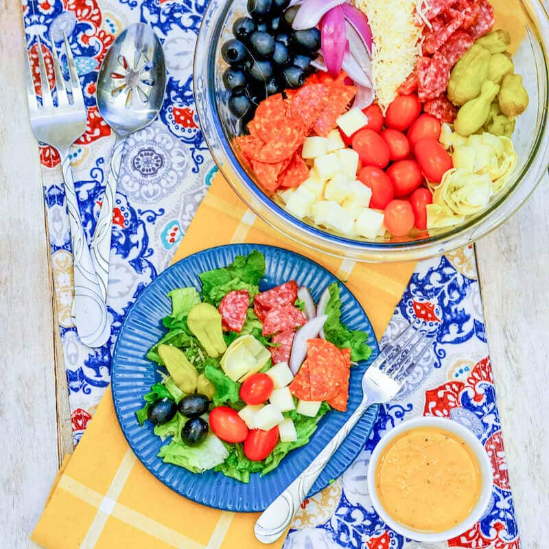 Overhead shot of a big bowl of antipasto salad and a serving of the salad on a blue plate.