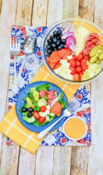 A blue plate of antipasto salad on top of a yellow dish towel.