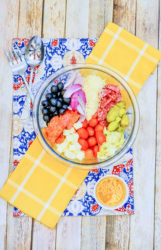 A big bowl of antipasto salad next to a small dish of dressing, and serving utensils.