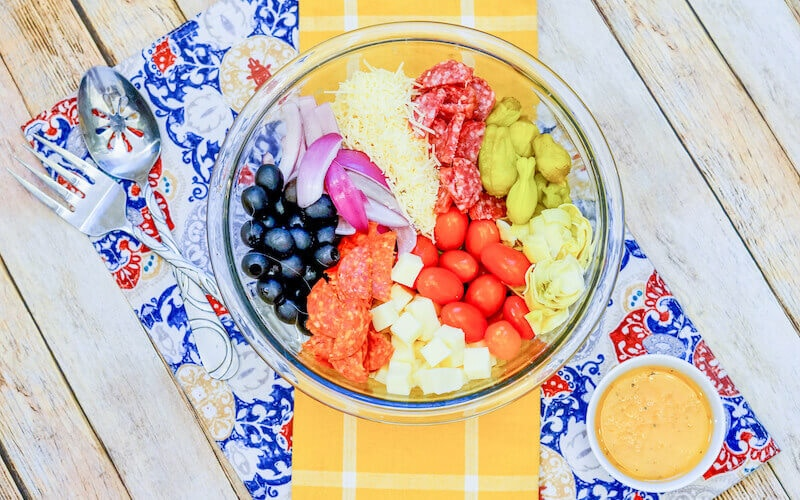 A yellow dish towel underneath a bowl of antipasto salad.