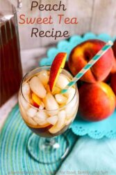 A glass of peach tea filled with ice next to a bowl of peaches.