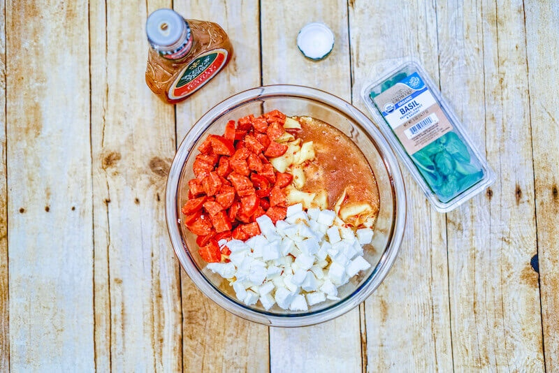 Overhead shot of all ingredients for pepperoni pasta salad in a glass bowl.
