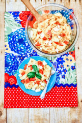 Pasta salad on a red and blue colorful placemat.