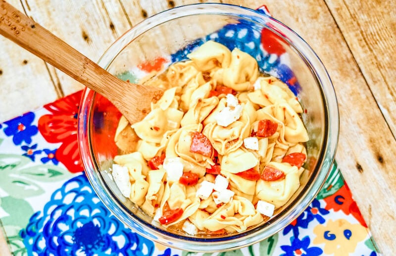 Glass bowl of pepperoni pasta salad with wooden spoon sticking out.
