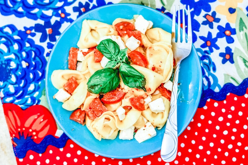A blue plate of pepperoni pasta salad topped with fresh basil.
