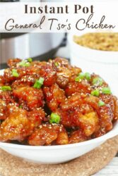 A bowl of general tso's chicken topped with sliced green onions.