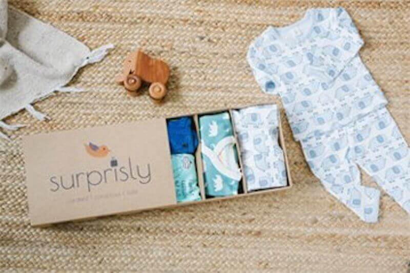 A box that says Surprisly, next to a pair of baby pajamas.