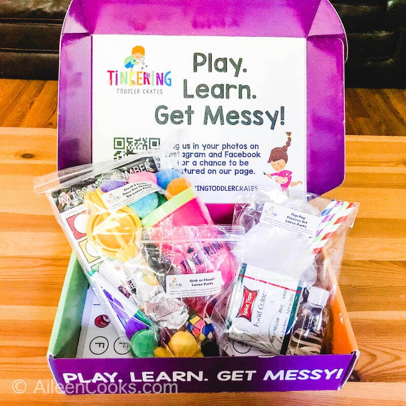 A purple box that says play, learn, get messy.