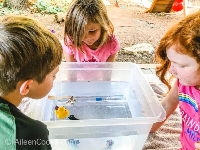 Three kids looking into a clear bin of water and various items.