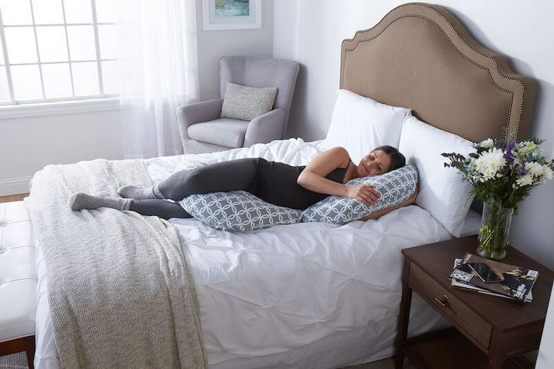 Woman laying on bed with a full size pregnancy pillow.