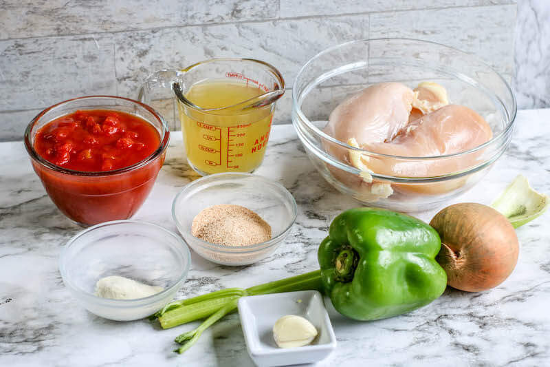 Ingredients for chicken creole on a marble countertop.