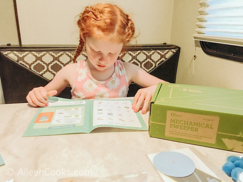 A little girl reading the instructions for kiwi crate.