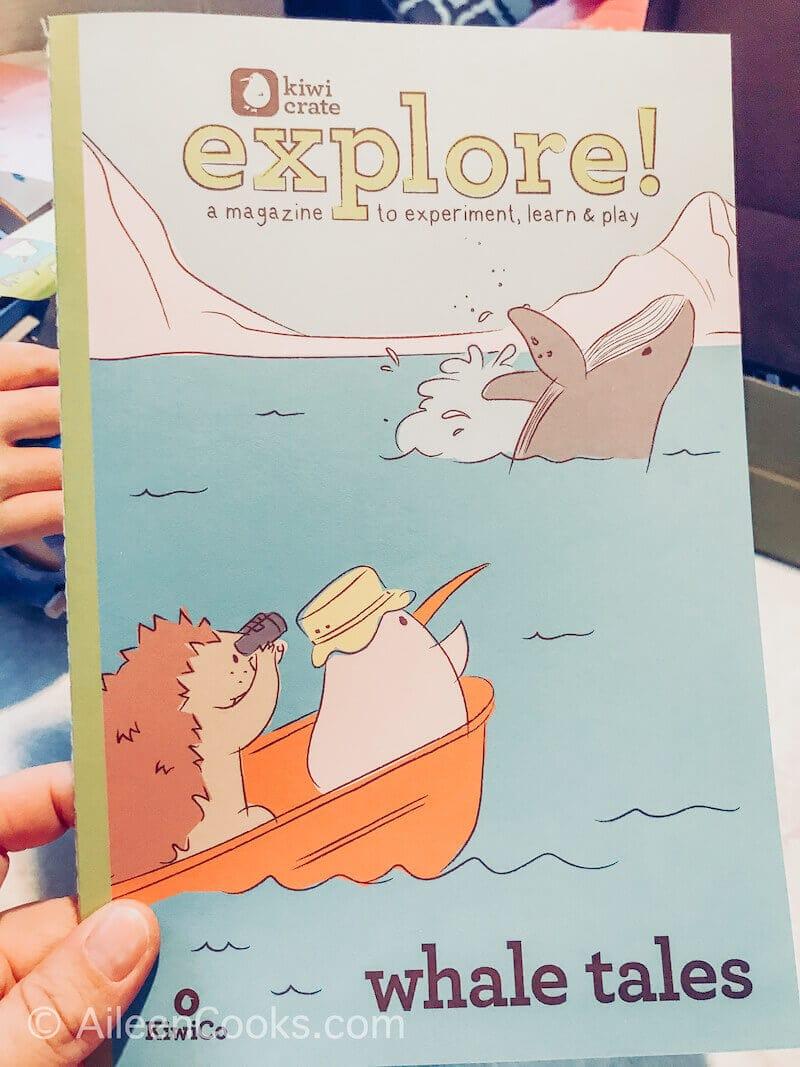 A hand holding the explore magazine from KiwiCo.