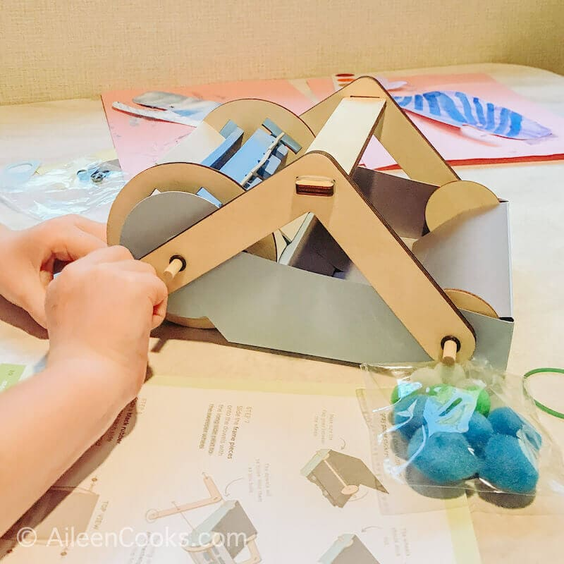 A child's hands building a mechanical sweeper.