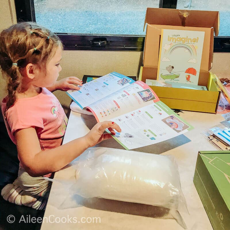 A little girl looking at the instruction booklet for her Koala Crate.