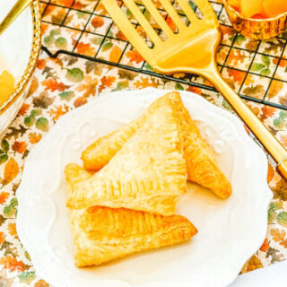 Three apple hand pies stacked up on a white plate.