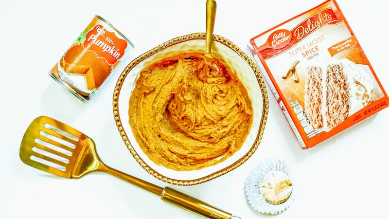 A bowl of cake mix and pumpkin mixed together.