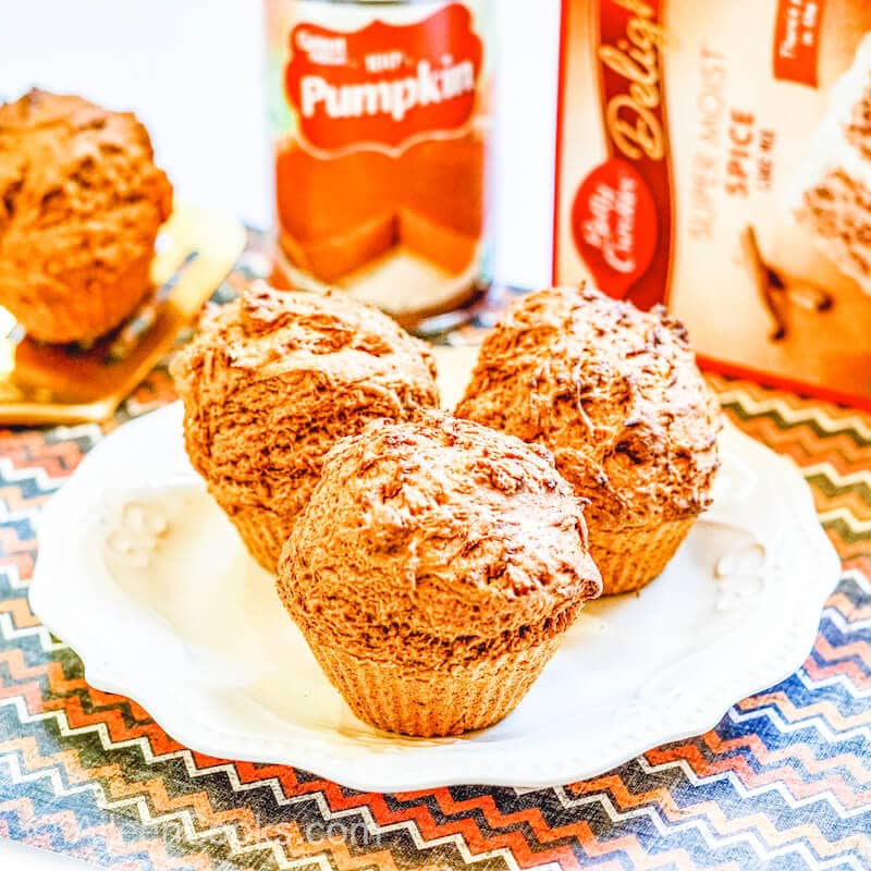 Three muffins in front of a can of pumpkin and box of spice cake mix.