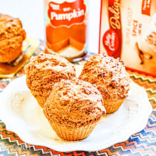 Three pumpkin muffins on a fancy white plate.