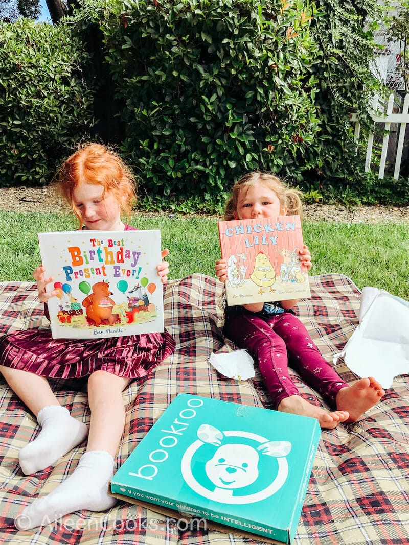 Two girls holding up new picture books.