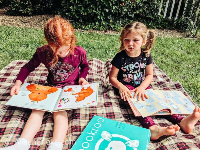 Two girls looking at picture books outside on a picnic blanket.