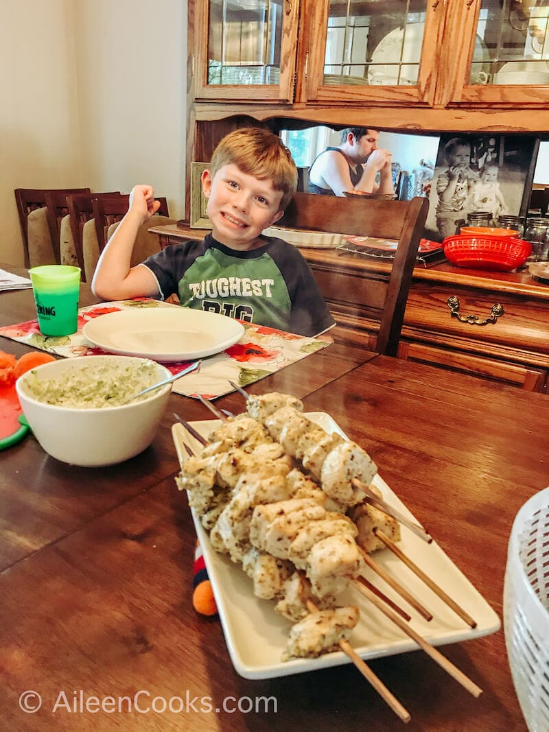 A tray of chicken skewers in front of a smiling boy.