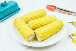 A white plate with four ears of corn on the cob, next to a blue butter dish.