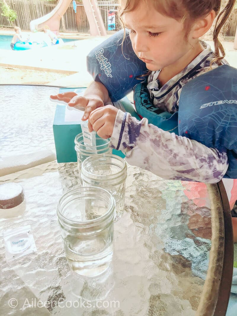A little girl pouring seeds into a glass of water.