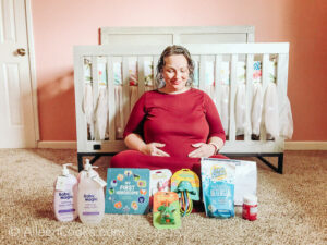 A pregnant woman in a red dress holding her belly in front of a crib and posing next to the contents of the New Mom and Baby Box.