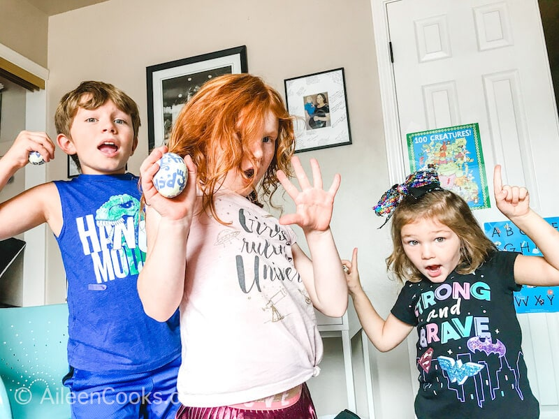 Three kids dancing and holding egg shakers.