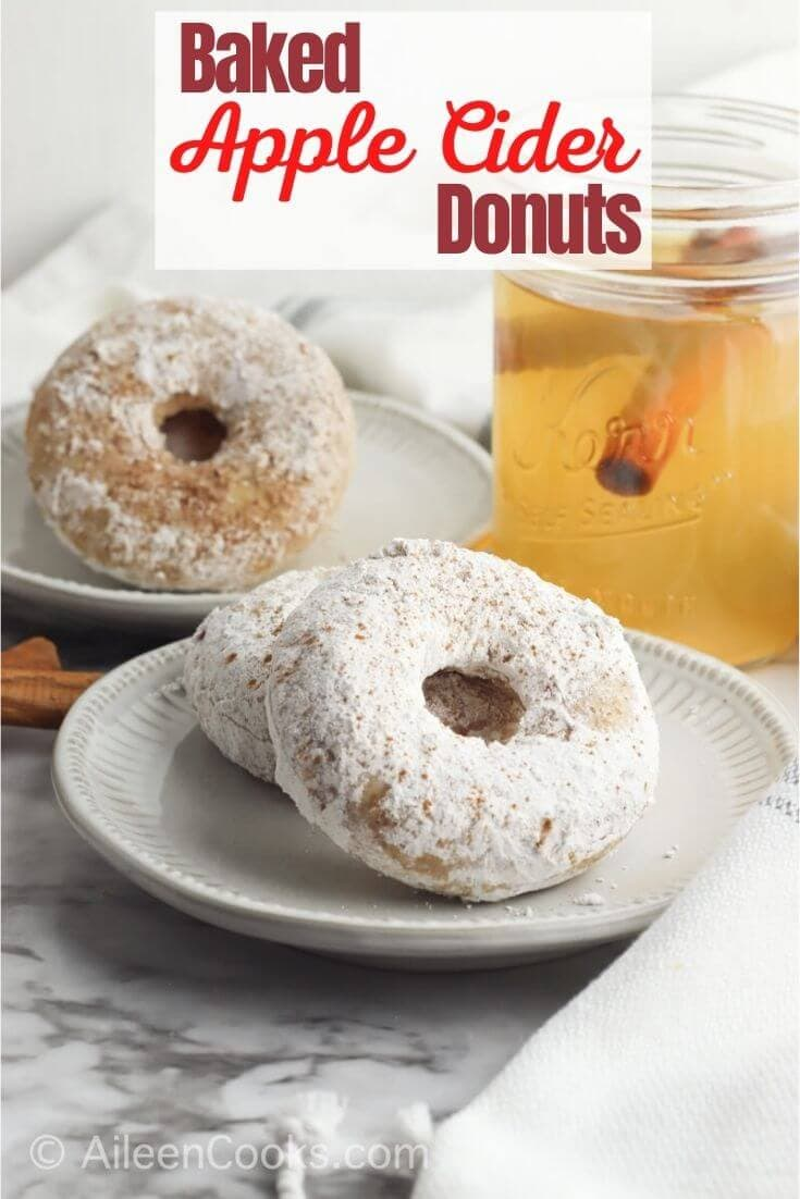 "A white plate of two powdered sugar donuts with the words ""baked apple cider donuts"" in red lettering."