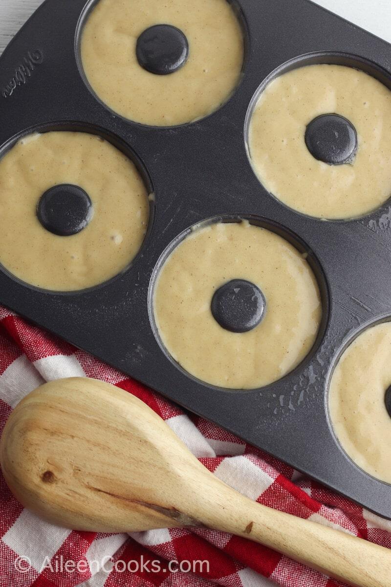 Apple cider donut batter inside donut pans.