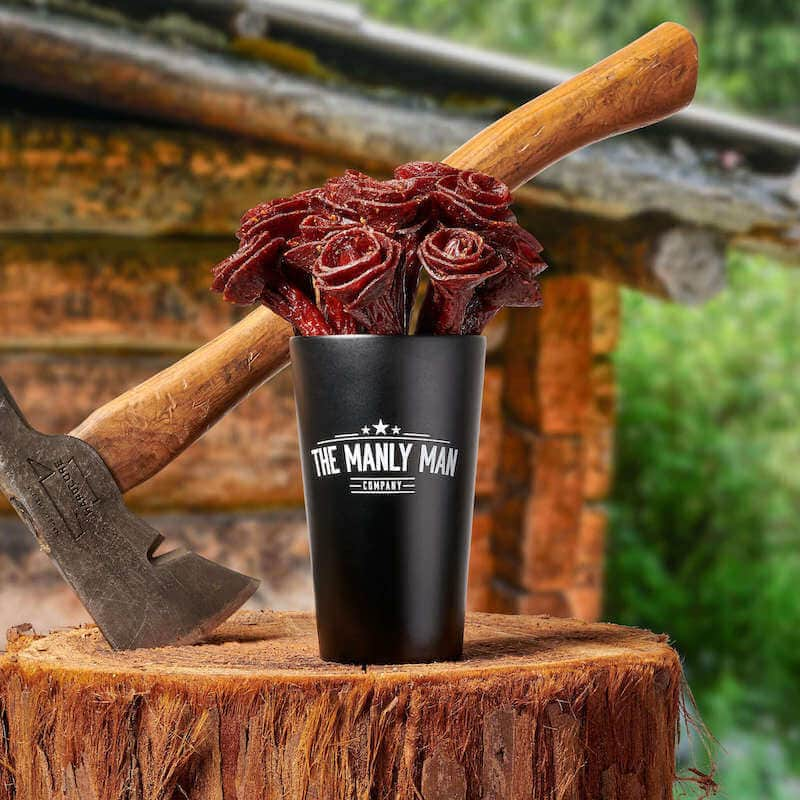A bouquet of jerky roses in a black mug next to an ax