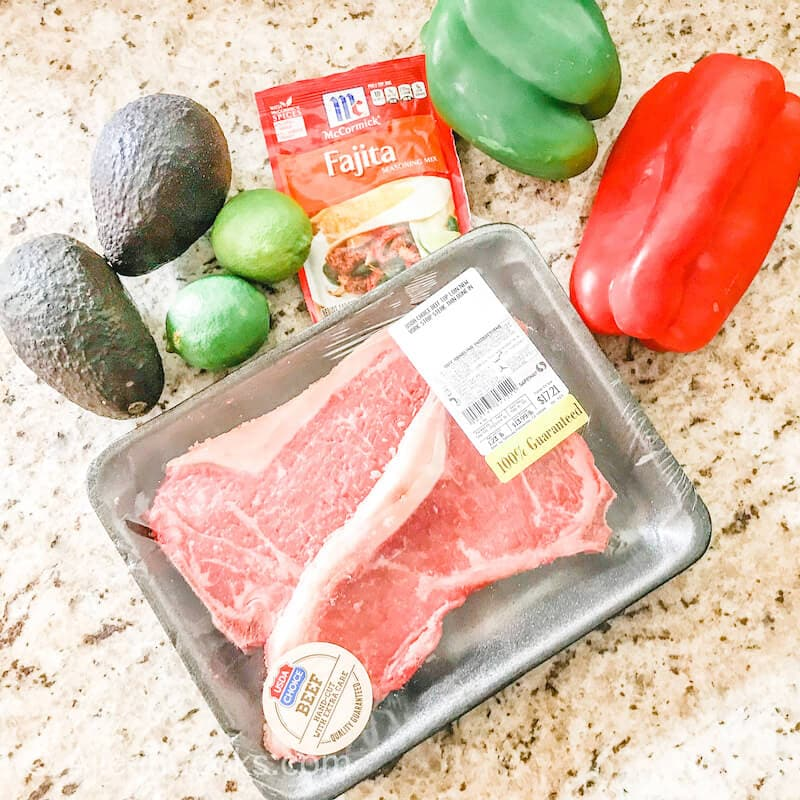 Ingredients for steak fajitas on a beige countertop.