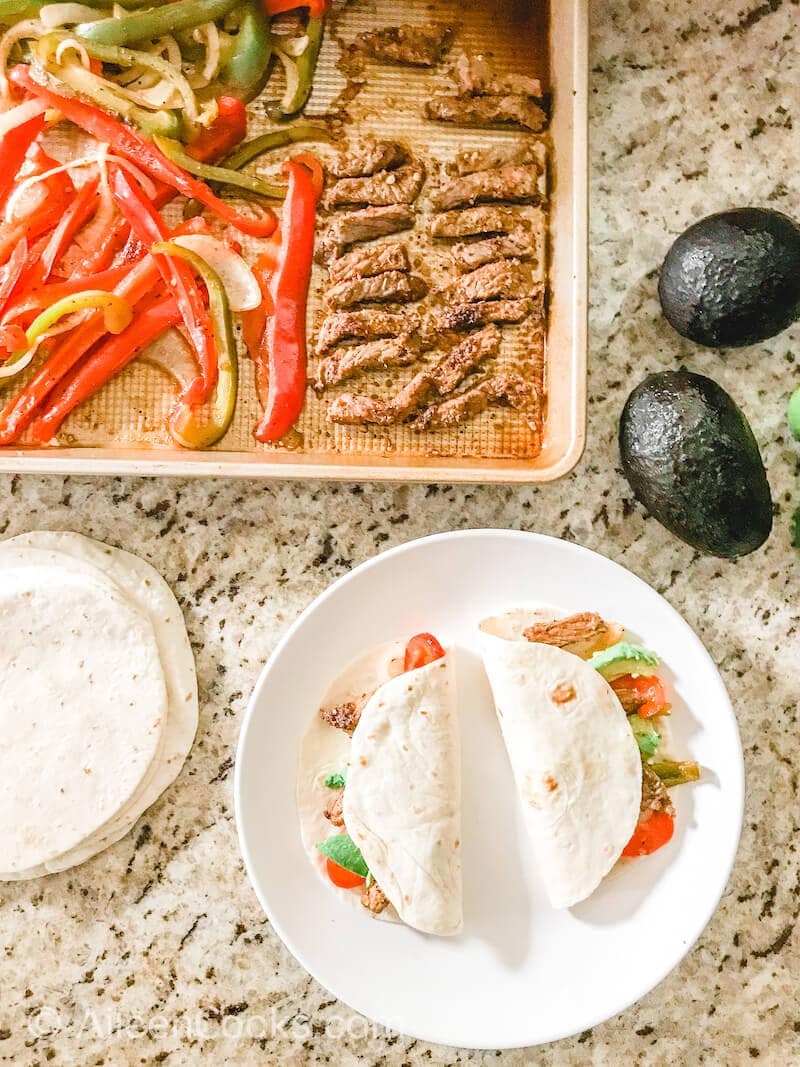 Overhead shot of two fajitas on a white plate above a sheet pan of steak and veggies.