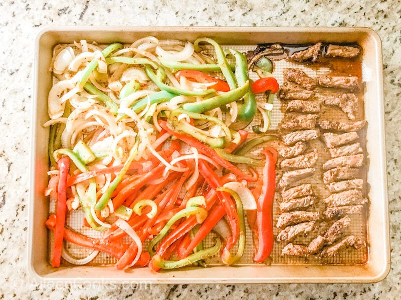 Cooked fajita meat and vegetables on a sheet pan.