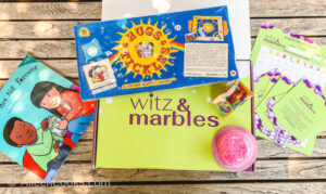 "A green box with the words ""Witz & Marbles"" along with the activities included in the box."